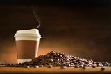 Paper cup of coffee  and coffee beans on old wooden background