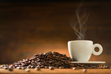 Cup of coffee with smoke and coffee beans on  wooden background © amenic181