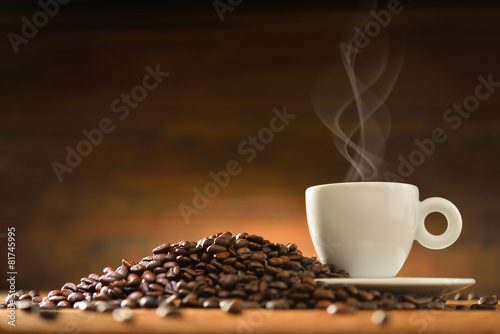 Foto op Canvas Koffie Cup of coffee with smoke and coffee beans on wooden background