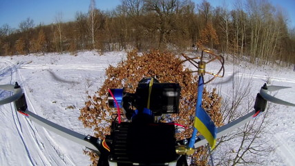 Drone with  flag of Ukraine fly up over tree. Aerial  winter