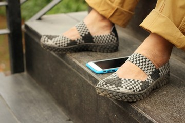 Smart phones place beside shoes at the park