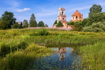 Russian landscape with small tranquil river and old church in th