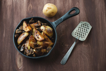 Pan with roasted unpeeled potatoes and mushrooms, above view
