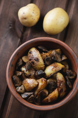 Ceramic bowl with roasted potato and mushrooms, above view