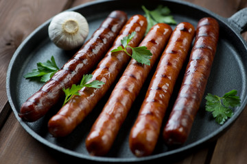Grilled sausages with parsley and garlic in a frying pan