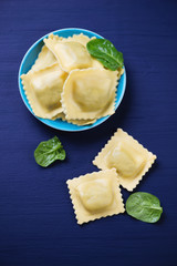 Ravioli with ricotta and spinach over dark blue wooden surface