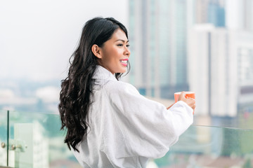 Asian woman in morning front of city skyline