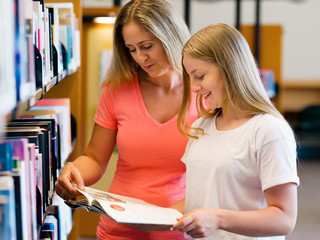 Girl and her mother in library