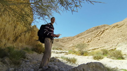 Backpacker in mountains with map