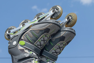 Raised feet putting on to rollerblades against a blue sky
