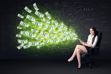 Businesswoman sitting in chair holding tablet with dollar bills