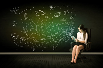 Businesswoman sitting in chair holding tablet with media icons