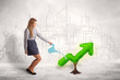 Business woman watering green plant arrow