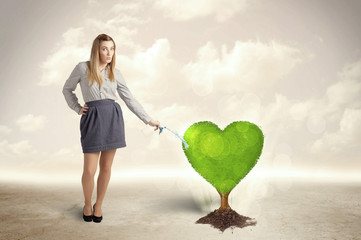Business woman watering heart shaped green tree
