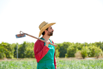 Farmer man with hoe looking at his field