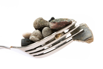 Concept about hard digestion. Fork with stones