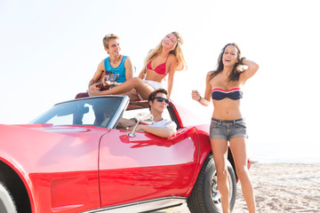 friends group at beach in sports car convertible