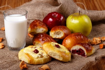 Fresh cherry pies, tarts, apples and glass of milk on the bag