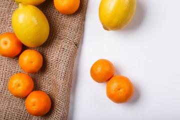 Fresh yellow lemons with orange mandarins on white background