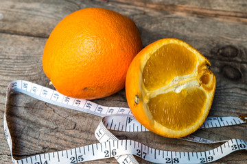 Orange  with measuring tape on old wood background
