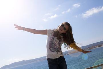 Niña con gafas de sol y brazos abiertos junto al mar