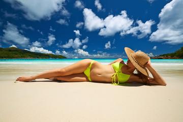 Woman in yellow bikini lying on beach at Seychelles