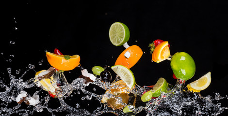 Mix of fruits with water splashes on black
