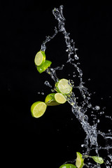 Limes with water splashes on black background © Jag_cz