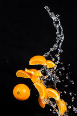 Oranges with water splashes on black background