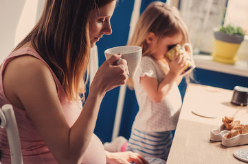 pregnant mother and child daughter having breakfast at home