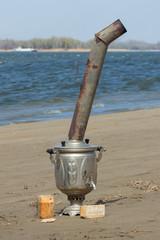 samovar on the wet sand near river