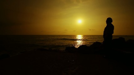 Man stands at Mediterranean sea looking at sunset , Lebanon