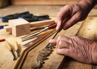The hands of an senior carpenter restoring old furniture