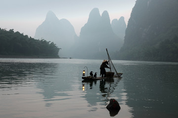 Chinese man fishing with cormorants birds in Yangshuo, Guangxi r