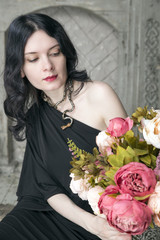 Brunette young woman in black dress with flowers