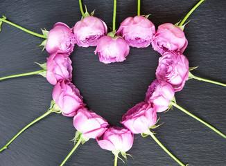Herz aus Rosenblüten auf Schiefer