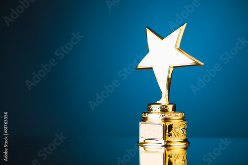 Leinwanddruck Bild gold star trophy against blue background