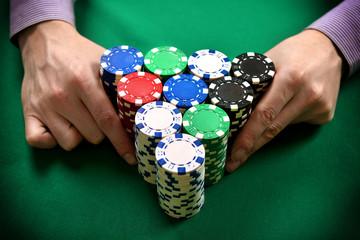 dealer moves poker chips