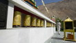 Tibetan Buddhist prayer wheels in Buddhism temple. Man traveler