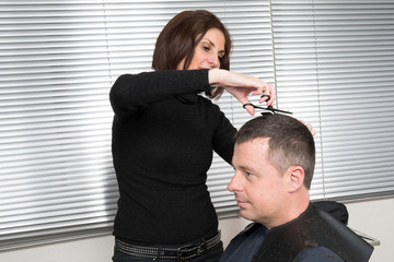 Hairstylist combing  client in hairdressing beauty salon