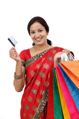 Young smiling traditional woman with shopping bags and credit ca