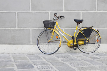 Old yellow bike on a stone pavement against a plaster wall