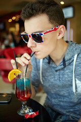 Teeanger boy drinking nonalcoholic cocktail in a restaurant