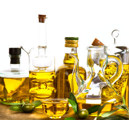 Olive oil. Bottles and jars of extra virgin olive oil over white