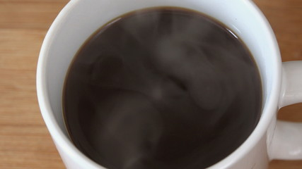Pouring Cream or Milk in Hot Warm Steaming Black Coffee