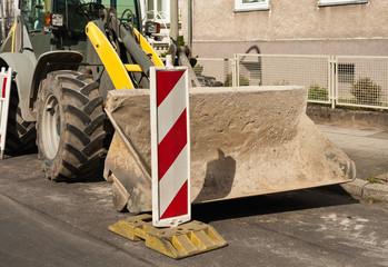 Strassenbau - Ein grosser Radlader parkt am Strassenrand