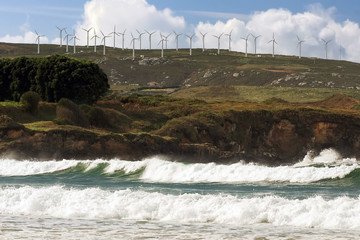 beach landscape with wind turbines  farm in the background