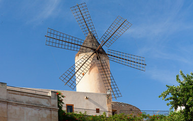 Old style windmill on the blue sky
