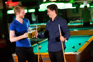 Young men playing pool and drinking beer