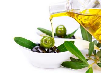 Olive oil. Pouring virgin olive oil on olives